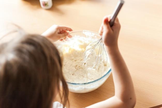 Meisje bereiden ontbijt, bakken, roer in een kom met bloem, melk, eieren, pannenkoeken, kinderen helpen moeder, familie ontbijt, koken