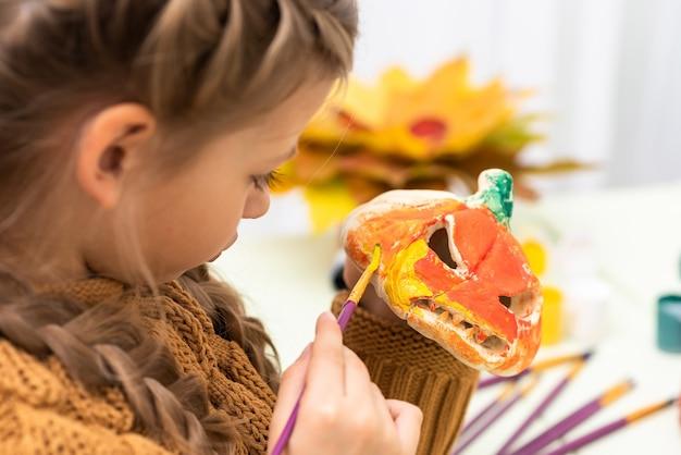 Meisje bereidt een pompoen voor op de halloween-vakantie.