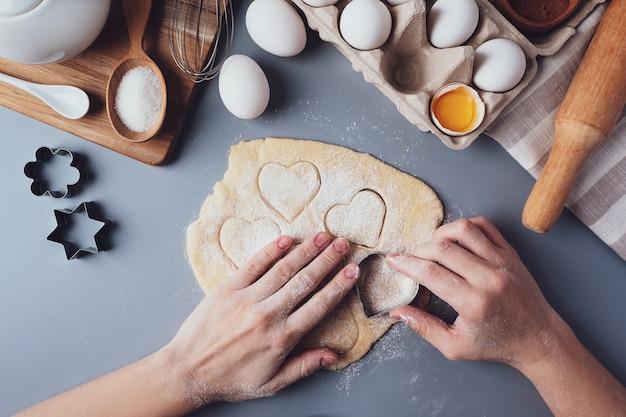 Meisje bereidt koekjes in de vorm van een hart, platliggende compositie op een grijze achtergrond. koekjessnijders en deeg in de handen van vrouwen. concept van voedsel voor valentijnsdag, vaderdag, moederdag.