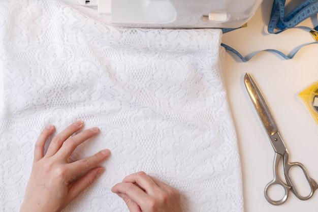 Meisje bereidt stof voor naaien op naaimachine, bovenaanzicht
