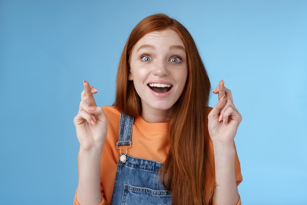Meisje beseft gebeden vervulde dromen komen uit goed nieuws horen staand verrast geamuseerd glimlachen breed grote ogen onder de indruk kruis vingers veel geluk eindelijk verlangen wens bereikt blauwe achtergrond