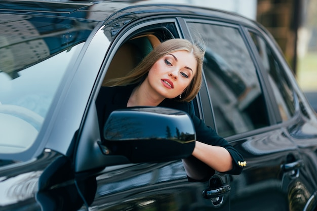 Meisje bestuurt een auto en kijkt uit raam op verkeersopstopping