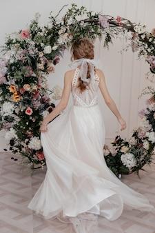 Meisje beweegt prachtig in een lange witte elegante jurk