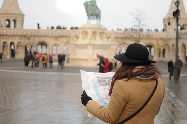 Meisje bezienswaardigheden. vrouw alleen kijken naar de kaart om de stad te zien. winter koude tijd. reis naar het buitenland.
