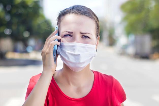 Meisje, bezorgde vrouw in beschermend steriel medisch masker op haar gezicht die ambulance roepen, die op cel mobiele telefoon in openlucht op aziatische straat spreken. luchtverontreiniging, virus, chinees pandemisch coronavirusconcept