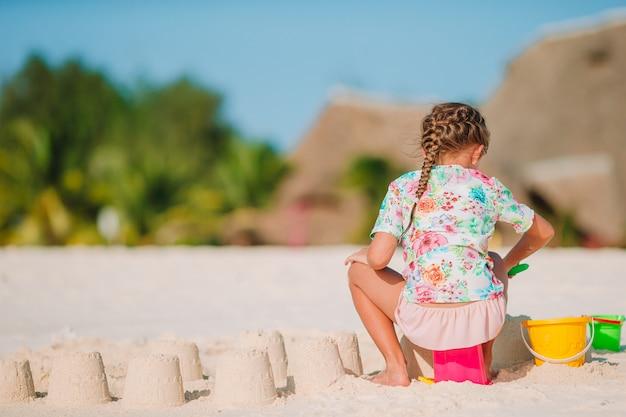 Meisje bij tropisch wit strand dat zandkasteel maakt