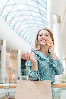 Meisje bij winkelcomplex die op de telefoon spreken