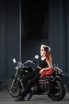 Meisje biker seksueel poseren op motorfiets 's nachts stad