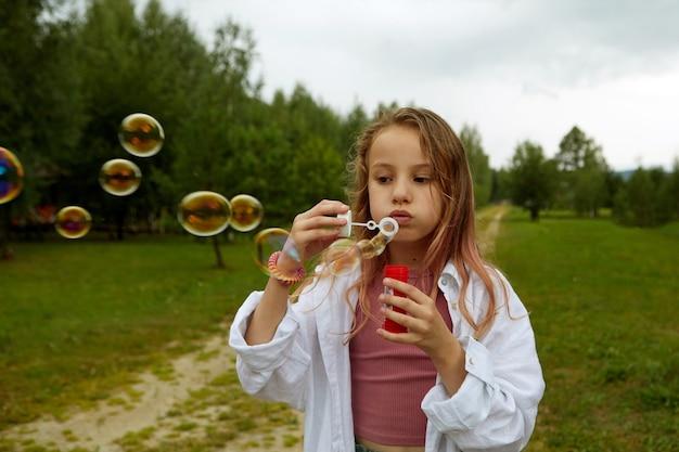 Meisje blaast bellen in groen gazon op het platteland