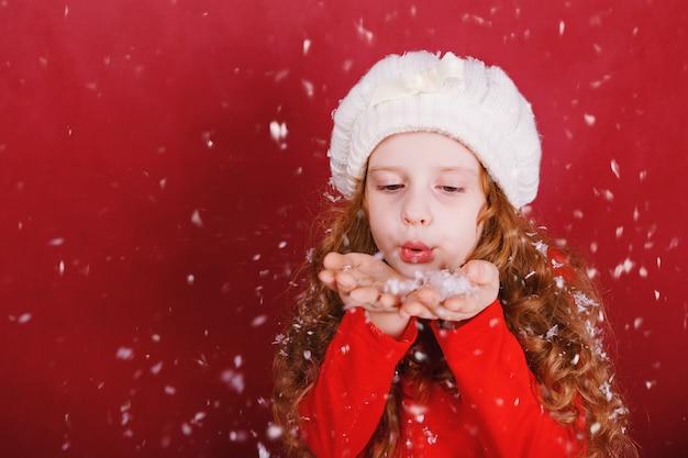 Meisje blazende sneeuw met haar hand.