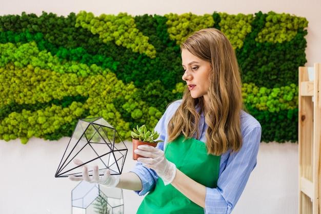 Meisje bloemist tuin planten in glazen vorm, zand, vetplanten, handschoenen, mos, interieur