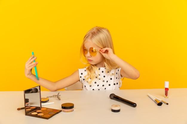 Meisje blogger in de gele studio voor camera maken van video. werken als blogger, video-tutorials opnemen voor internet.
