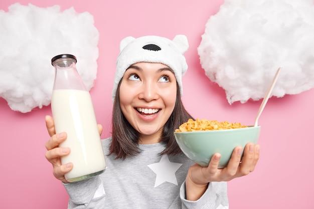 Meisje boven geconcentreerd met een gelukkige glimlach gekleed in comfortabele nachtkleding poses met ontbijtgranen en melk heeft een gezond ontbijt