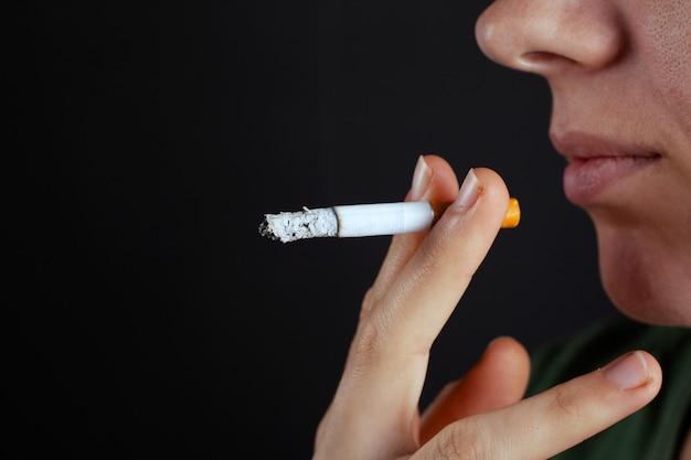 Meisje brengt een sigaret op haar gezicht. schade door het roken van nicotineclose-up.
