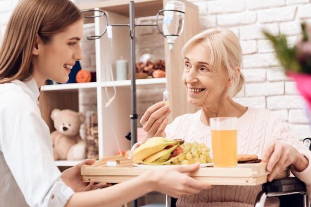 Meisje brengt ontbijt vrouw eet fruit
