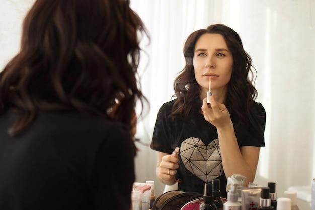 Meisje brunette zet make-up voor de spiegel, reflectie in de spiegel