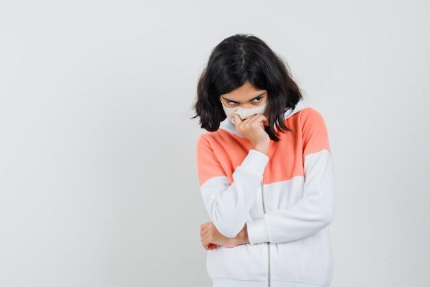 Meisje buigt hoofd naar beneden, houdt hand op mond in jas, masker en kijkt boos. vooraanzicht.