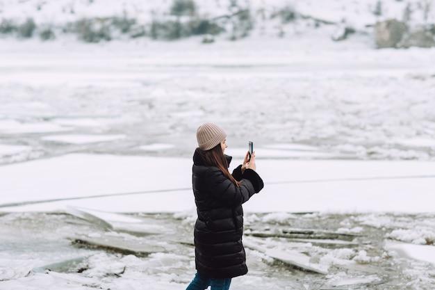 Meisje buiten lopen en het nemen van foto op mobiele telefoon de bevroren rivier.