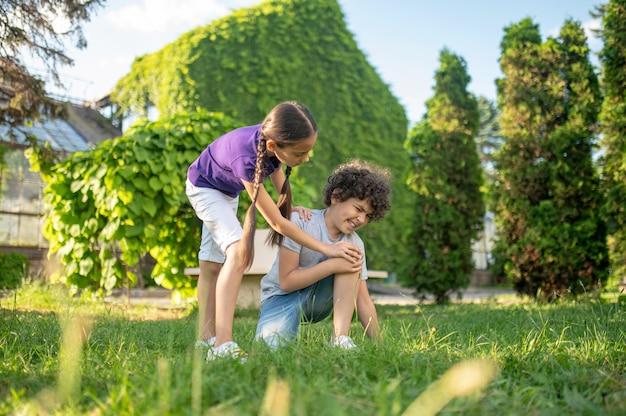 Meisje bukken voor jongen zittend op gras