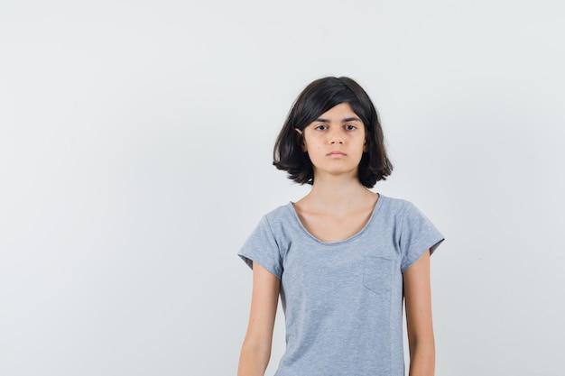 Meisje camera in t-shirt kijken en kalm, vooraanzicht kijken.