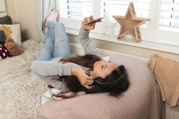 Meisje checkt haar telefoon in bed Gratis Foto