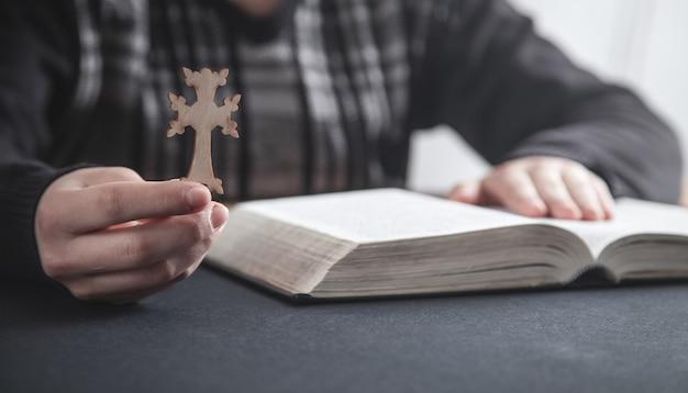 Meisje christelijk kruis houden en bidden over bijbel