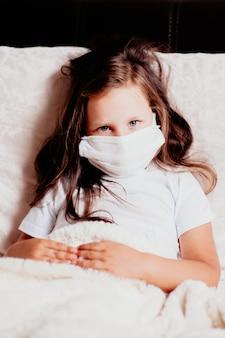 Meisje close-up zittend in een wit masker op het bed in de slaapkamer, zelfisolatie met een verkoudheid, de tweede golf van virussen.