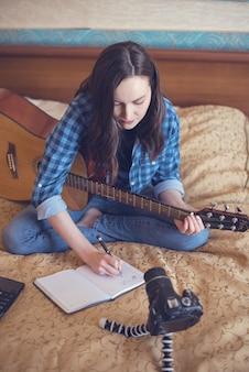 Meisje componist schrijft in laptop componeren van muziek op gitaar en bloggen op camera