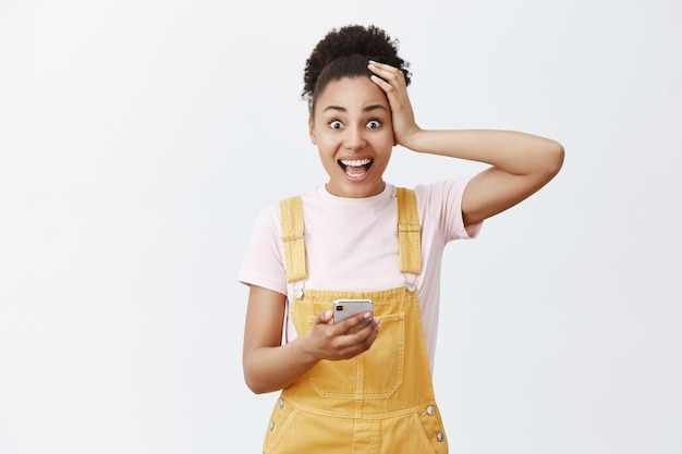 Meisje controleerde de kalender, herinnerde zich een geweldige gebeurtenis. portret van schattige onder de indruk en verrast afro-amerikaanse vrouw in gele overall, haar aan te raken en lachend van opwinding, mobiel vast te houden