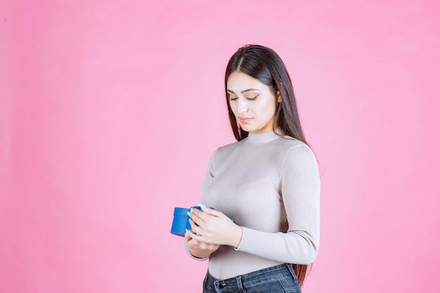Meisje controleert haar blauwe geschenkdoos en kijkt opgewonden en verrast