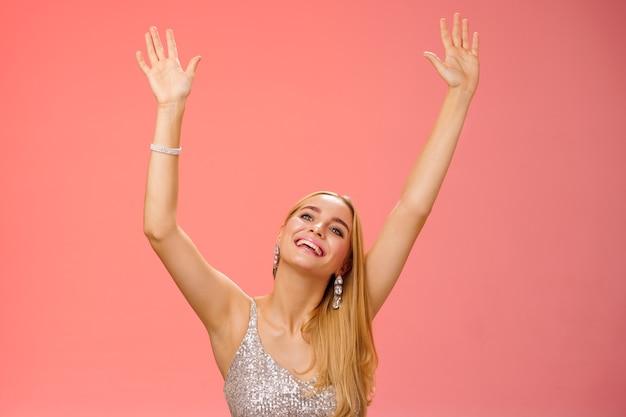 Meisje dansen met plezier staand fanzone feest genieten van geweldig concert favoriete zanger in zilveren glinsterende elegante jurk handen omhoog zwaaien met palmen bewegend muziekritme glimlachend opgetogen