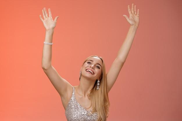Meisje dansen met plezier staande fanzone partij genieten van geweldige concert favoriete zangeres in zilveren glinsterende elegante jurk