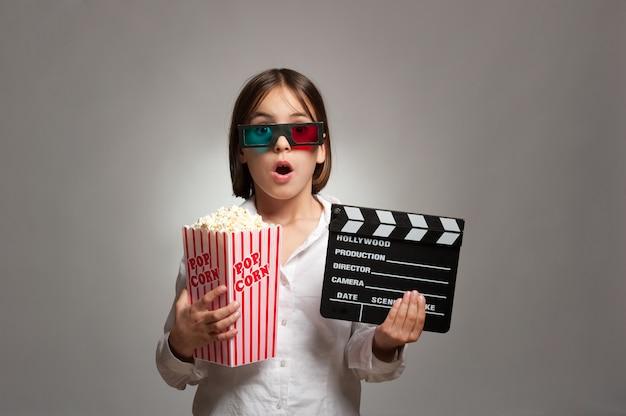 Meisje dat 3d-bril draagt en popcorn eet