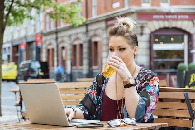 Meisje dat aan haar computer en het drinken van bier werkt