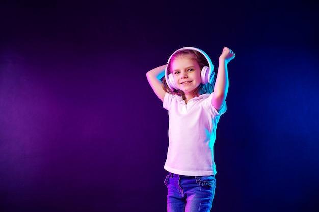 Meisje dat aan muziek in hoofdtelefoons op donkere kleurrijke muur luistert. leuk kind dat van dansmuziek geniet,