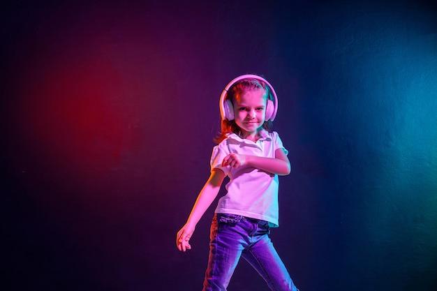 Meisje dat aan muziek in hoofdtelefoons op donkere kleurrijke muur luistert. neonlicht. dansend meisje. gelukkig klein meisje dat op muziek danst. leuk kind dat van gelukkige dansmuziek geniet.