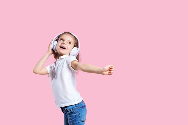 Meisje dat aan muziek in hoofdtelefoons op roze luistert. leuk kind dat van gelukkige dansmuziek geniet, sluit het oog en glimlach het stellen
