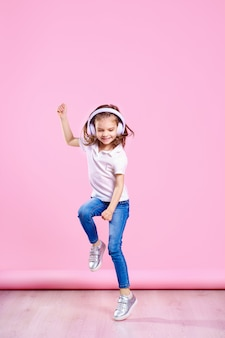 Meisje dat aan muziek in hoofdtelefoons op roze muur luistert. dansend meisje. gelukkig klein meisje dat op muziek danst. leuk kind dat van gelukkige dansmuziek geniet.