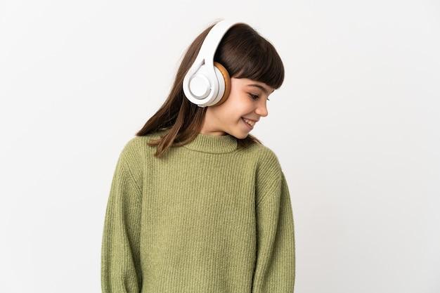 Meisje dat aan muziek met mobiel luistert die op witte muur wordt geïsoleerd die aan muziek luistert