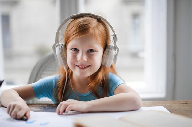 Meisje dat aan muziek op hoofdtelefoons luistert
