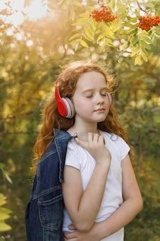 Meisje dat aan muziek op hoofdtelefoons luistert.
