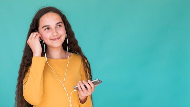 Meisje dat aan muziek op oortelefoons luistert