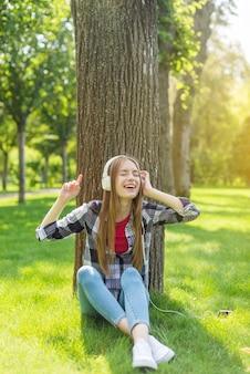 Meisje dat aan muziek op witte hoofdtelefoons luistert