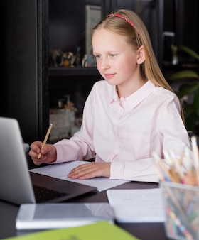 Meisje dat aantekeningen maakt in online klasse