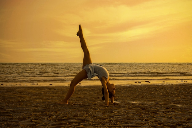 Meisje dat acrobatische bewegingen uitvoert bij het strand in de zonsondergang
