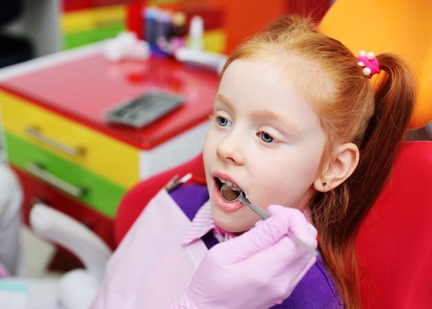 Meisje dat als rode tandvoorzitter glimlacht. de tandarts onderzoekt de tanden van de patiënt van het kind.