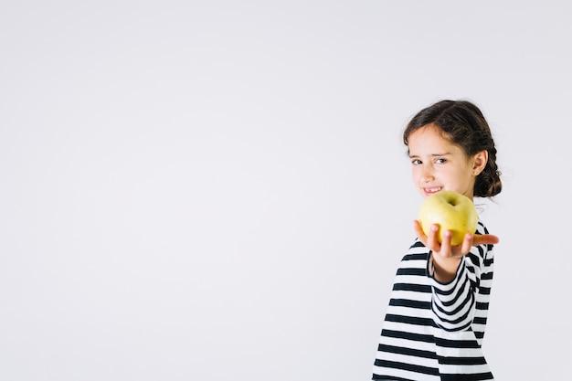 Meisje dat appel aanbiedt
