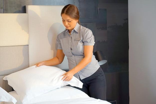 Meisje dat bed in hotelkamer maakt. huishoudster bed opmaken