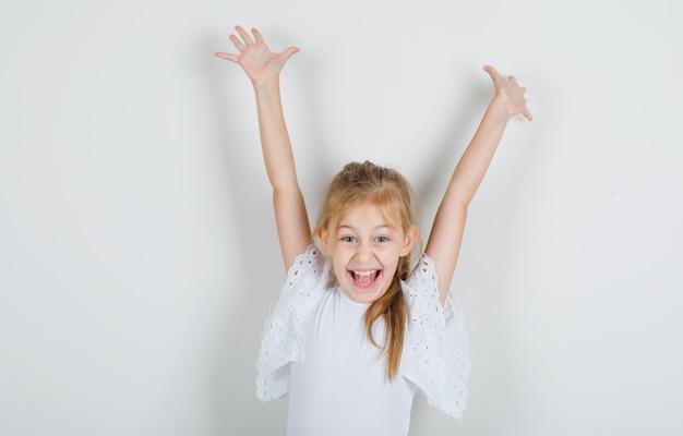 Meisje dat beide handen in wit t-shirt opheft en vrolijk kijkt