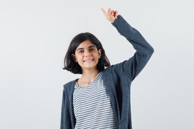 Meisje dat benadrukt door arm in t-shirt, jasje op te heffen en gelukkig te kijken.